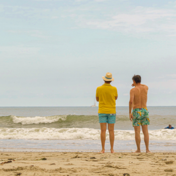two men in shorts facing the sea